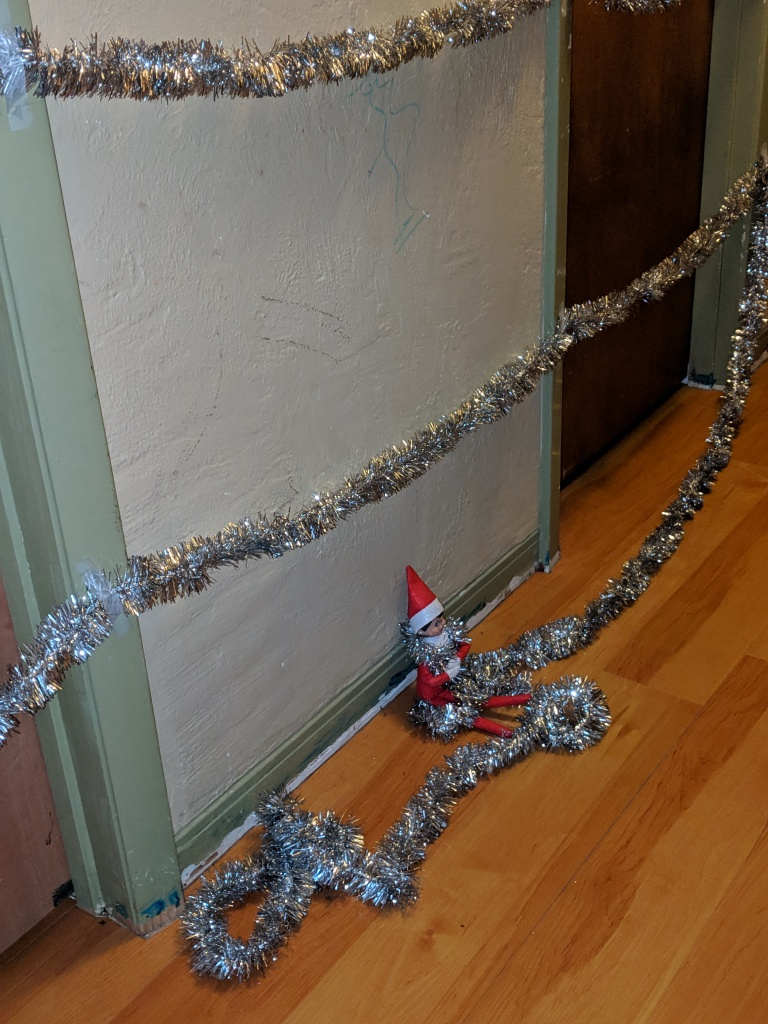 Elf tangled in silver garland. ELf had strung the garland across the bedroom doors.