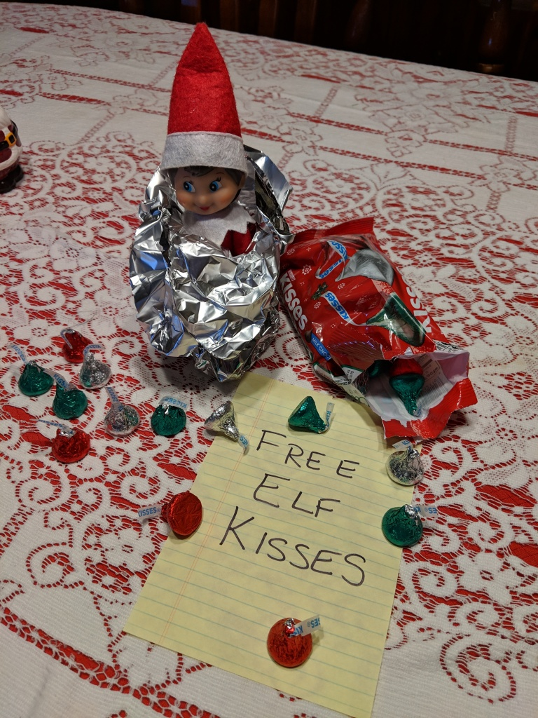 Elf wrapped in foil like a giant chocolate kiss candy.
