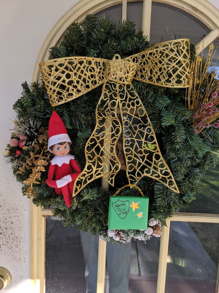 Elf in a Christmas wreath with her suitcase.
