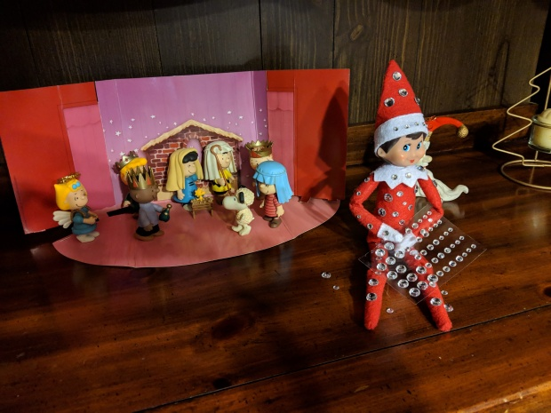 Elf on the shelf sitting in front of a Charlie Brown nativity scene, placing rhinestones on her outfit.